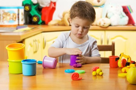 Almost 2 years old child playing plasticine in childrens room