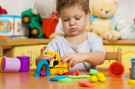 2 years old child playing plasticine in childrens room