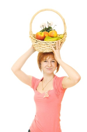 Young red-haired caucasian woman holding backet full of fresh fruits on her head  photo