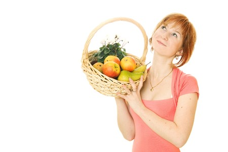 Young red-haired caucasian woman holding backet full of fresh fruits and looking upside photo