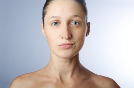 Right part of woman's face is serious, other one is smiling. Young woman without any makeup. 写真素材