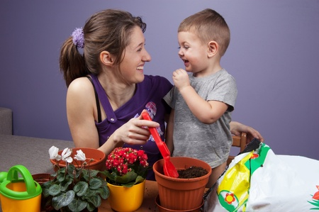 replanting: Child and his mother replanting flowers at home