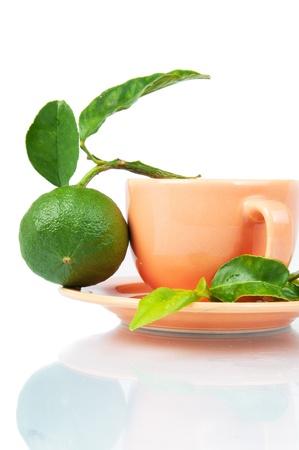 A cup of bergamot tea, bergamot orange fruit and fresh bergamot leaves