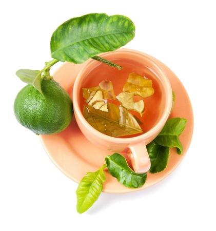 A cup of bergamot tea, bergamot fruit and fresh bergamot tree leaves