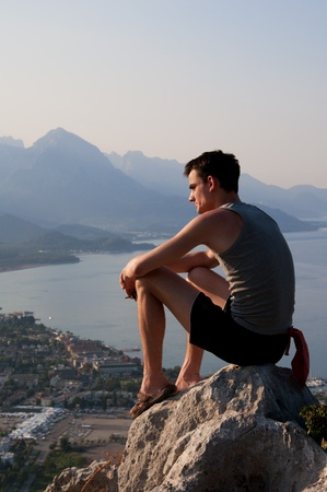 far away look: Young man sitting on the rock high above the city