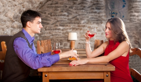Young beautiful couple drinking wine in medieval restaurant photo