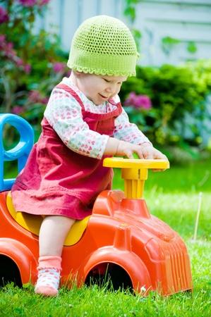 Adorable baby riding a toy car in the garden photo