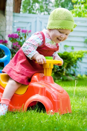 Adorable baby riding a toy car in the garden