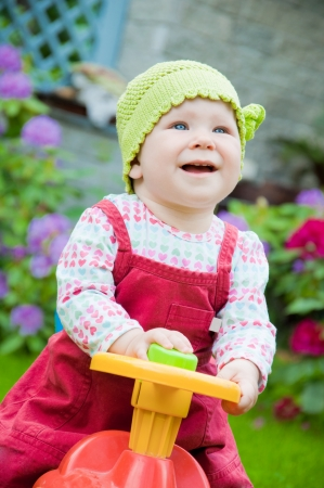 Adorable baby riding a toy car in the garden photo