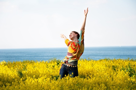 Young happy woman dancing in yellow flowers Stok Fotoğraf