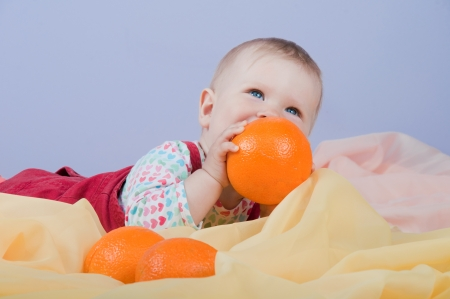 Adorable baby-girl playing with oranges photo