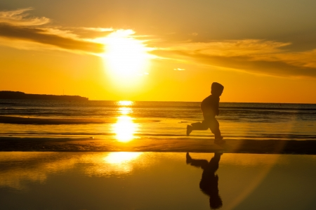 Silhouette of a child running on the beach Stock Photo