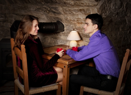 Young beautiful couple sitting in medieval cafe drinking tea photo