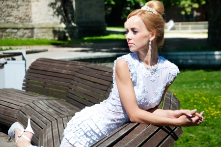 Beautiful bride sitting on the bench in the park