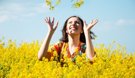 Young happy woman throwing yellow flowers
