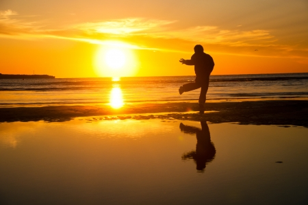 Silhouette of a dancing boy on the beach Stock Photo