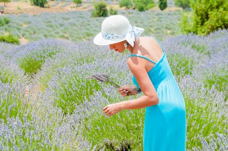 Beautiful young woman in long blue dress posing in lavander field, Turkey, Burdur