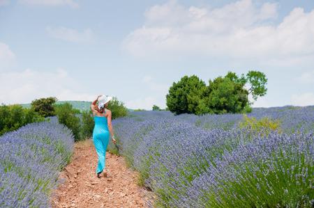 lavanda: Beautiful young woman in long blue dress posing in lavander field, Turkey, Burdur