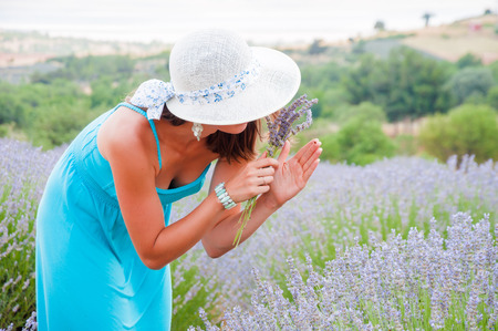 Beautiful woman looking at a ladybug on her hand in lavander field