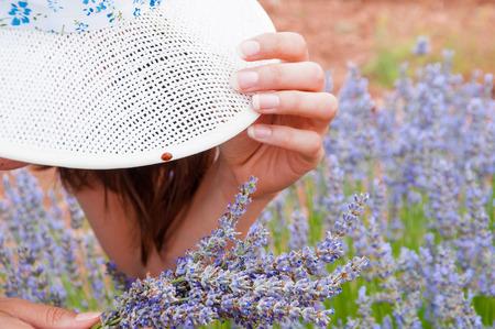 Closeup of straw hat, ladybug and lavander