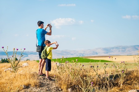 Father and son taking pictures of beautiful view onto the field and mountains in Turkey, Sandikli Stock Photo