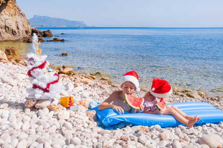 floatable: Children in Santa hats eating watermelon on the beach Stock Photo
