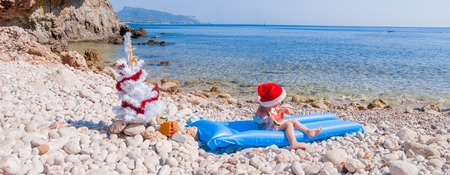 floatable: Little pretty girl in Santa hat eating watermelon on the beach