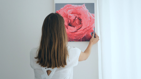 Long-haired girl hanging painting on wall at house Stock Photo - 70700021