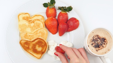 Heart-shaped pancakes with strawberry on a white dish. Simple breakfast for Valentines Day Stock Photo