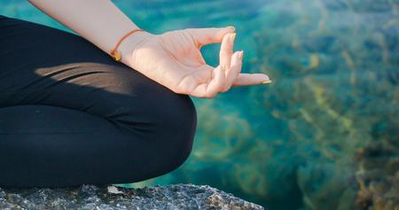 Female hand in aakaash mudra yogic gesture, peaceful calm woman practices meditation near the sea outdoors, closeup