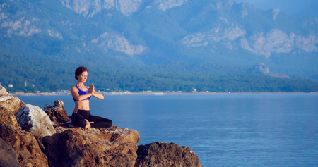 Girl practices yoga near the ocean during sunrise time Stock Photo