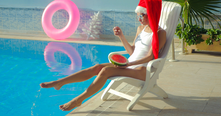 Christmas Woman eating watermelon at the Pool. Funny girl celebrating Christmas in a resort Stock Photo