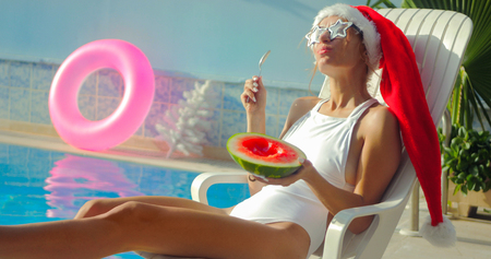 Christmas Woman eatig watermelon at the Pool. Funny girl celebrating Christmas in a resort
