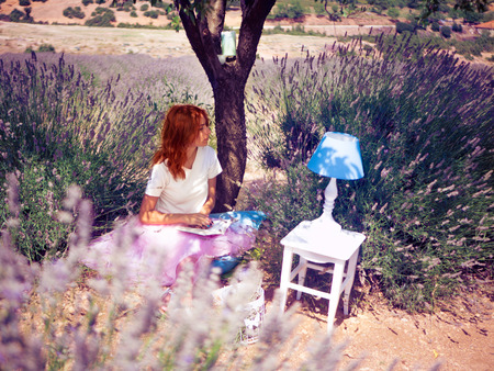 Young woman reading a book under the tree