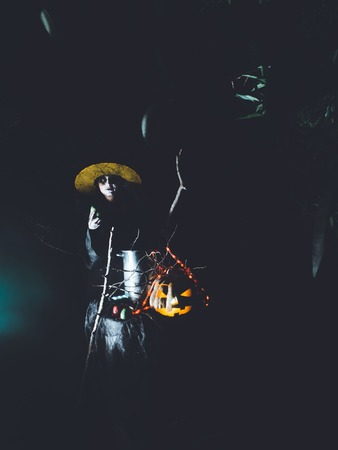 Wicked frightening witch hexing with cane above the cauldron in dark forest . Halloween Horror Scene 스톡 콘텐츠