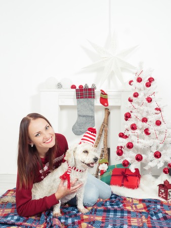 beautiful woman having fun with her dog, both dressed with christmas clothes, sitting on the floor by Christmas tree Stock Photo