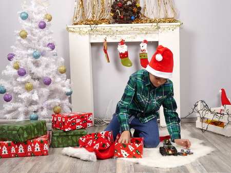 Boy in Christmas hat opens presents near small white Christmas tree Stock Photo