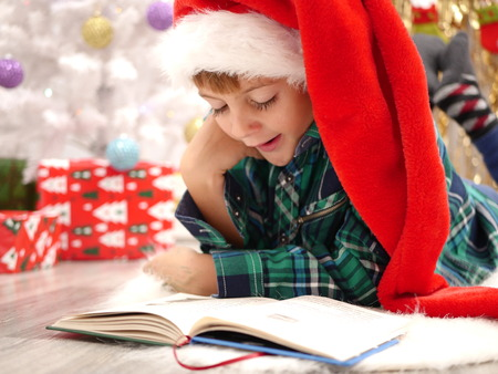 Boy in long Christmas hat reading a book and yawns on the floor by the white Christmas tree