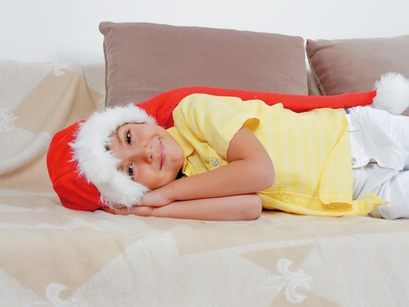 Cute boy in Christmas hat and yellow shirt laying on the sofa Stock Photo