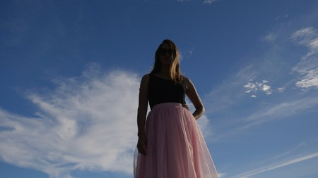 Fashion lifestyle portrait of young happy pretty woman in pink tulle skirt on blue sky background