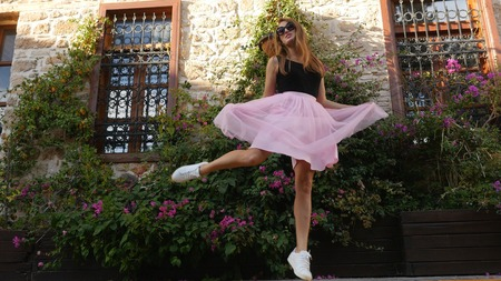 Fashion lifestyle portrait of young happy pretty woman in pink tulle skirt jumping on street background