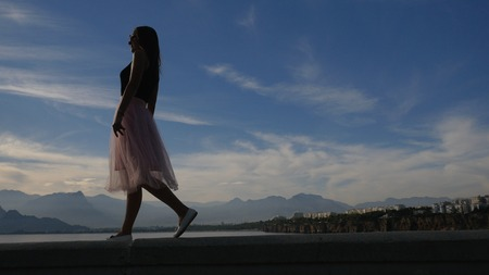 Fashion lifestyle portrait of young happy pretty woman in pink tulle skirt walking on blue sky background 免版税图像