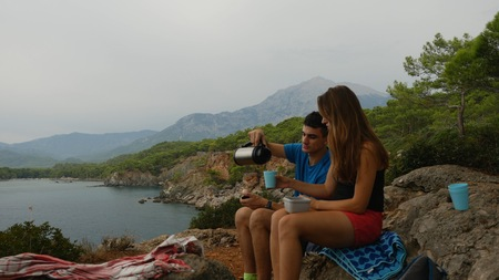 Happy couple sitting on the rock and drinking hot tea in mountains. Family concept