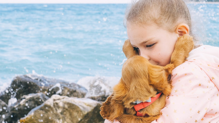 Portrait of little girl sitting on the rocks near the sea with her sweet cocker spaniel puppy, spring time