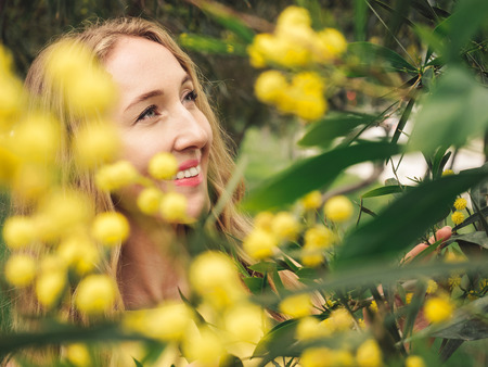 Portrait of young beautiful smiling woman with long blond hair in yellow dress standing under spring Australian Golden wattle tree in spring garden. Zdjęcie Seryjne
