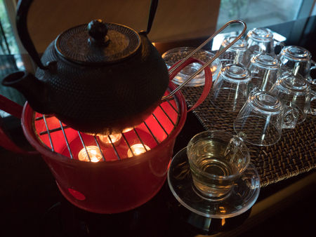 brown teapot standing on a pink steel heater with a candles and glass  tea mug