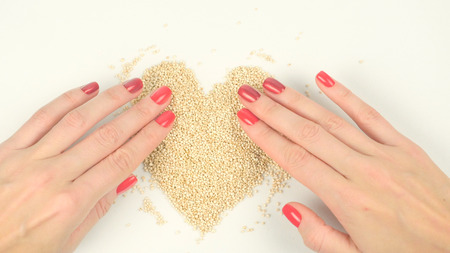 Closeup of womans hands forming heart from quinoa seeds Stock Photo
