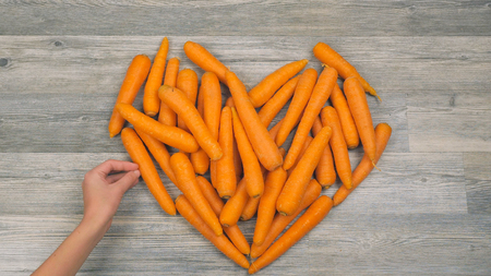 Closeup of childs hands put carrots in the shape of a heart on a white background in fast motion. Healthy food concept