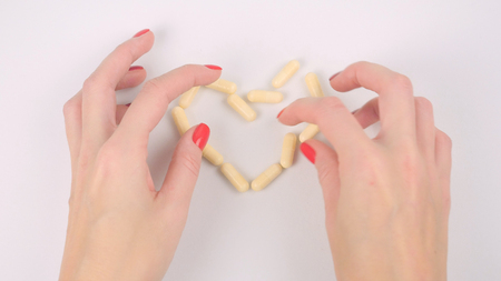 Womans hands making heart shape yellow capsule pills on white table