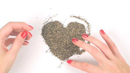 Closeup of womans hands forming heart from chia seeds in backward play Stock Photo